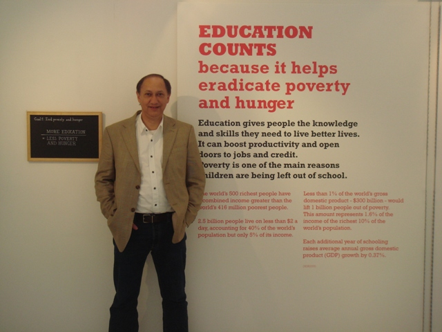 Chris standing next to the Education Counts exhibition inside the UN Building