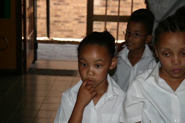 The learners from Alpha school are watching with interest as Johann and Basil start to dispense the glasses.