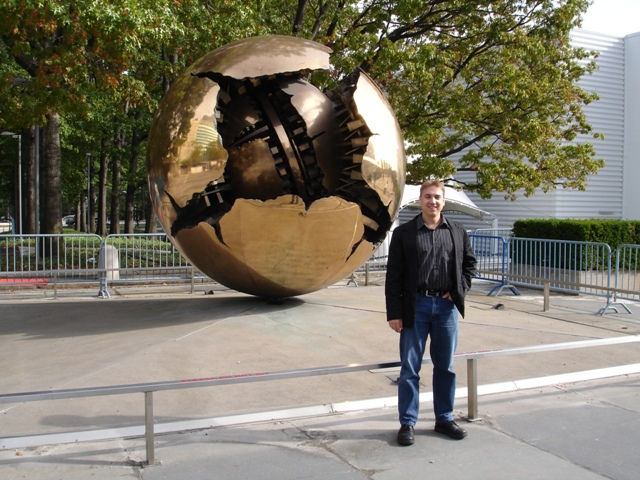 Charl standing in front of the Sphere within a sphere statue