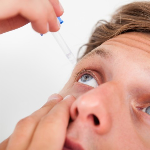 Close up of male inserting eye drops