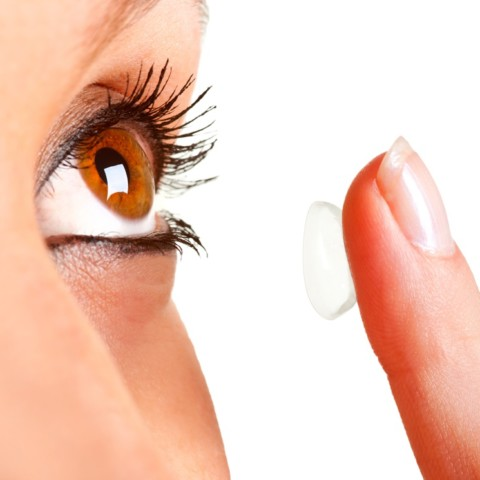 Close up of a woman inserting a soft contact lens
